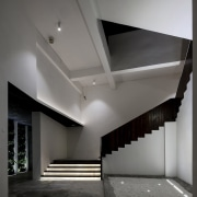 On the ground floor, you're guided by recessed architecture, black and white, ceiling, daylighting, house, interior design, light, monochrome, product design, gray, black