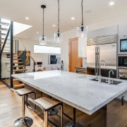 The kitchen is open and inviting, with hanging countertop, interior design, kitchen, real estate, gray