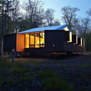 At night, the elevated cabin lights up architecture, cottage, home, house, hut, log cabin, real estate, shack, shed, tree, black