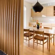 This large lamp dominates the kitchen, acting as dining room, floor, flooring, furniture, hardwood, interior design, laminate flooring, light fixture, room, table, wall, wood, wood flooring, brown, orange, white