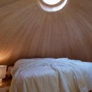 This skylight illuminates the bedroom bed, bedroom, ceiling, daylighting, floor, flooring, interior design, light, lighting, plaster, room, suite, wall, wood, wood stain, brown
