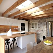 The historical part of the home is on beam, ceiling, countertop, cuisine classique, flooring, interior design, kitchen, living room, loft, real estate, wood flooring, brown, gray