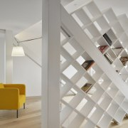 A bookshelf breaks up this large living space architecture, ceiling, daylighting, floor, home, interior design, loft, product design, shelf, stairs, wall, gray