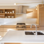 This spacious island features plenty of room for cabinetry, countertop, floor, furniture, interior design, kitchen, lighting, plywood, product design, white