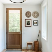A large hanging light is the focal point ceiling, daylighting, floor, home, house, interior design, room, wall, window, wood, white