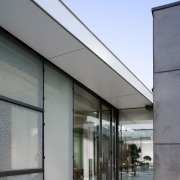 The roof wraps around into a soffit architecture, building, facade, glass, house, sky, gray