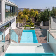 Greenery surrounds the property architecture, condominium, estate, home, house, leisure, property, real estate, resort, swimming pool, villa, teal