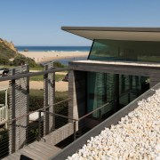 The roof echoes the nearby beach. The house architecture, handrail, house, property, real estate, walkway, black