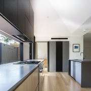 The island conceals the dishwasher and sink, while architecture, cabinetry, ceiling, countertop, daylighting, floor, hardwood, house, interior design, kitchen, laminate flooring, real estate, wood flooring, white
