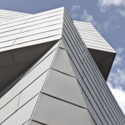 Like the surrounding rock formations, the observatory is angle, architecture, building, commercial building, daylighting, daytime, elevation, facade, line, roof, siding, sky, skyscraper, white, gray