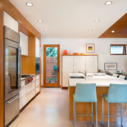 The kitchen features a spacious island with room cabinetry, ceiling, countertop, floor, interior design, kitchen, real estate, room, white