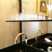 This gold faucet is a touch of elegance bathroom, ceiling, countertop, flooring, glass, interior design, light fixture, lighting, sink, orange, black