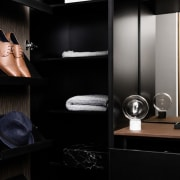 The walk-in wardrobe features angled, store-like shelves furniture, interior design, product design, room, black