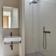 A large skylight illuminates the open shower bathroom, floor, interior design, plumbing fixture, product design, room, shower, tap, tile, wall, gray