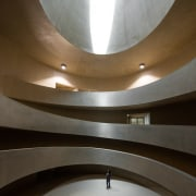 This massive volume channels the Guggenheim architecture, ceiling, daylighting, interior design, light, lighting, line, wall, brown, gray