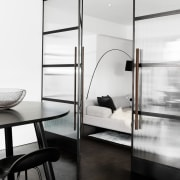 The doors separating the dining area from the black and white, floor, furniture, glass, interior design, product design, shelf, white, black
