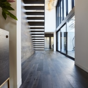 This wood floor runs along the floor and architecture, daylighting, floor, flooring, hardwood, home, house, interior design, laminate flooring, property, real estate, tile, wood, wood flooring, gray, black