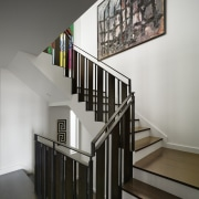 A single piece of art dominates the winding baluster, daylighting, glass, handrail, interior design, stairs, gray, black