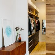 The open wardrobe juts out from the wall floor, furniture, home, interior design, room, shelf, shelving, wall, wood, white, orange, brown