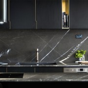 Stone counters and a stone splashback compliment the countertop, floor, flooring, interior design, kitchen, under cabinet lighting, black