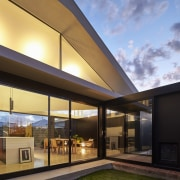 The home at dusk architecture, daylighting, facade, home, house, interior design, property, real estate, residential area, roof, window, brown