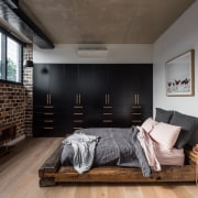 The bed in this room seems to fit architecture, floor, furniture, house, interior design, living room, loft, room, wood, black