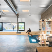 The office opens out to a courtyard architecture, ceiling, daylighting, floor, flooring, interior design, loft, table, wood, gray