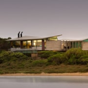 From the water, the home appears to rise architecture, cottage, home, house, landscape, property, real estate, roof, sky, gray, brown