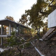The main living area is a glass sandwich architecture, cottage, home, house, plant, real estate, tree, black, gray, brown