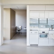 A simple kitchen reflects the bay cabinetry, countertop, floor, home appliance, interior design, kitchen, product design, gray