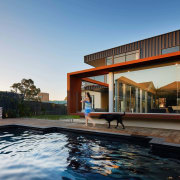 The home has a clear connection to the architecture, condominium, estate, facade, home, house, leisure centre, property, real estate, sky, swimming pool, villa, gray