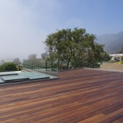 You can glimpse the mountains from this deck architecture, daylighting, deck, floor, house, outdoor structure, property, real estate, roof, wood, gray, red