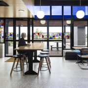 A cafe on the ground floor flows into chair, furniture, interior design, table, white, black