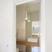 This powder room tucked off to the side, bathroom, bathroom accessory, bathroom cabinet, door, floor, home, interior design, plumbing fixture, room, sink, window, white
