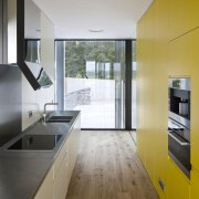 The kitchen has a cheery yellow feature wall architecture, ceiling, countertop, daylighting, floor, house, interior design, kitchen, real estate, room, wood flooring, gray
