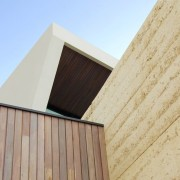 Concrete and wood intersect outside architecture, building, daylighting, facade, sky, wall, wood, orange
