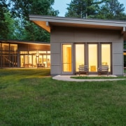 At night, the home lights up architecture, cottage, elevation, estate, facade, home, house, property, real estate, shed, siding, green, brown