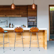 A simple three pendant light arrangement ensures even countertop, flooring, furniture, interior design, kitchen, table, gray