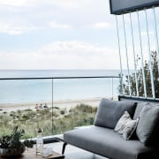 A glass balustrade keeps sea in full view chair, couch, furniture, home, interior design, living room, outdoor furniture, sea, sky, sunlounger, table, window, white