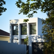 The home is situated on a leafy street architecture, building, elevation, estate, facade, home, house, real estate, residential area, sky, tree, window, teal, black