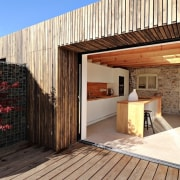 A sheltered outdoor area is perfect for entertaining architecture, facade, home, house, property, real estate, wood, orange, black