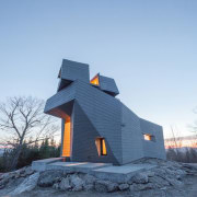 The observatory sits atop a granite outcropping architecture, building, cottage, farmhouse, home, house, roof, sky, snow, winter, teal