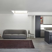 Without windows to let natural light in, the architecture, ceiling, floor, interior design, living room, room, table, wall, gray