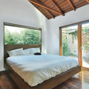 In the bedroom, plentiful use of glass and architecture, bed, bed frame, bedroom, ceiling, daylighting, estate, floor, hardwood, home, house, interior design, mattress, real estate, room, window, wood, wood flooring, gray, brown