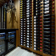 A spacious wine cellar sits off from the liquor store, wine cellar, winery, black, brown