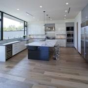The spacious kitchen keeps the island close countertop, floor, flooring, hardwood, interior design, kitchen, laminate flooring, real estate, tile, wood, wood flooring, gray