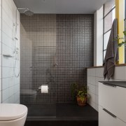 Recording studio or shower? This bathroom features an architecture, bathroom, floor, home, interior design, plumbing fixture, room, tile, toilet, wall, gray, black