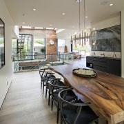 A long dining room features a unique table countertop, floor, flooring, interior design, kitchen, real estate, table, window, wood flooring, gray