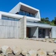 The garage door is hidden in the clean architecture, facade, home, house, property, real estate, gray