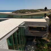 You can glimpse the beach nearby architecture, home, house, property, real estate, roof, black